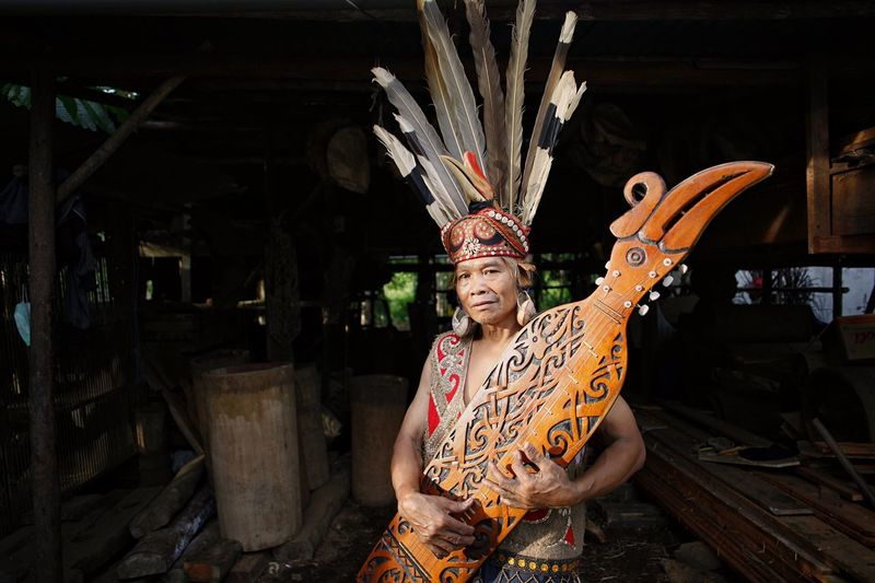 Portrait Of Woman Wearing Traditional Dress Holding Sape At Warehouse