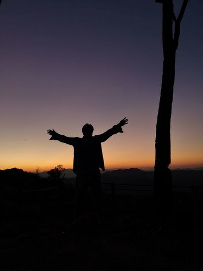 Silhouette man standing on field against sky during sunset