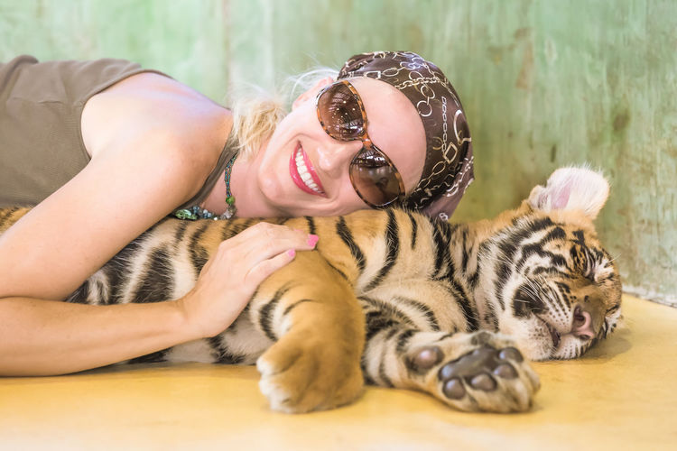Close-up of smiling young woman lying with tiger cub at zoo