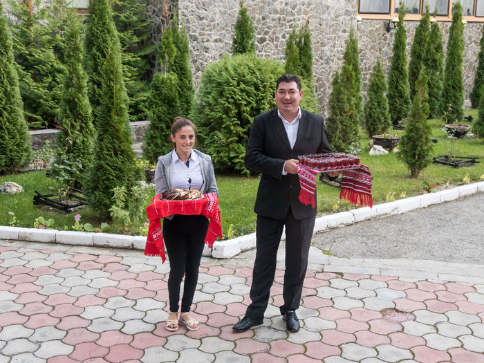 Poiana Brasov, Romania, October 04, 2017 : The staff of the hotel Mirage welcomes the guests with a treat at the entrance to the hotel in Poiana Brasov in Romania Business Employee Poiana Brasov Receptionist Romania Service Staff Travel Uniform Adult Architecture Concierge  Cultures Day Guest Hotel Job People Smiling Tourism Treat Tree Vacation Visitor Welcome