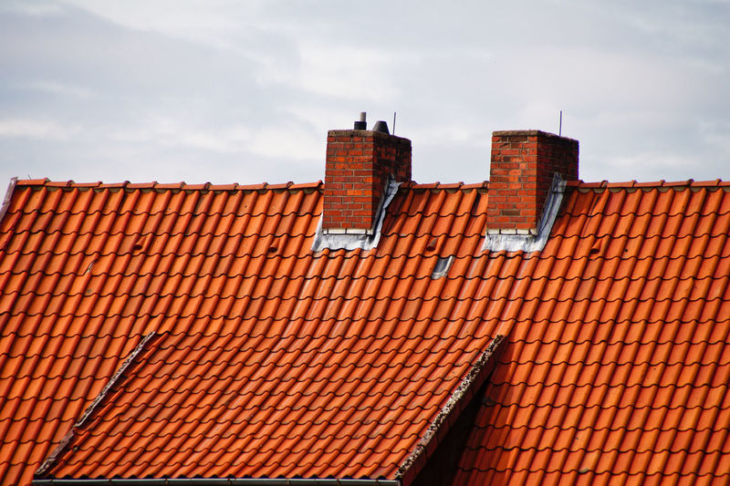 Roof Tiles On House Against Sky