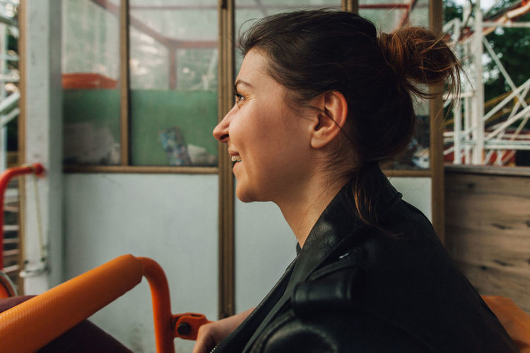 Portrait of young woman looking away while sitting in window