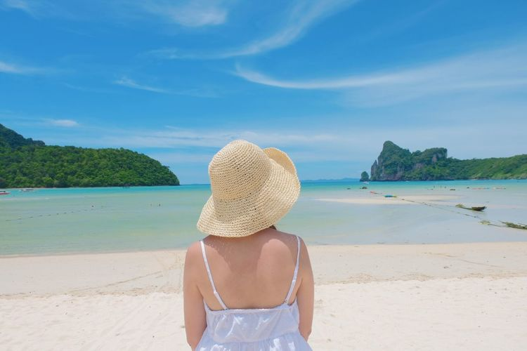 Rear View Of Woman Wearing Hat While Standing At Beach Against Blue Sky During Sunny Day
