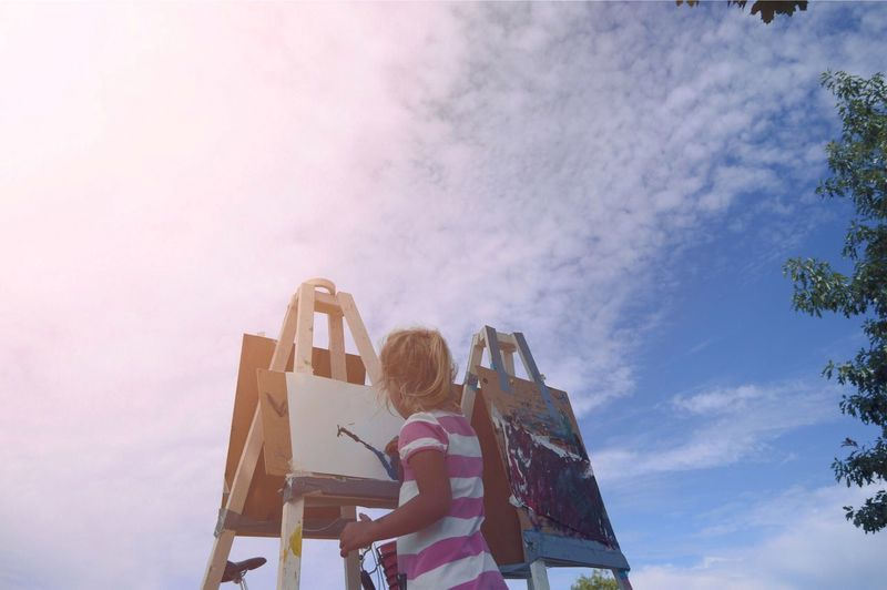 Low angle view of girl painting while standing against sky