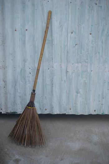 Broom against corrugated iron