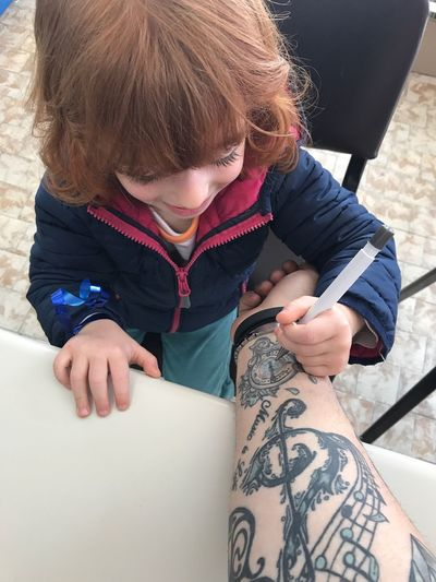 High angle view of boy drawing tattoo