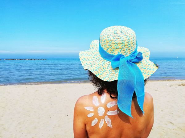 Abstract Conceptual Concept Sunscreen 2018 Summer2018 Hat With Bow Woman At The Sea Symbol Of The Sun Drawing With Sunscreen Symbol Sun Written With Sunscreen Sun Protection Protection Sunscreen Is Important Tanning Sunscreen Sunscreen On The Skin Sea Water Beach Sand Horizon Over Water Sun Hat Suntan Lotion Sunbathing Moisturizer Sandy Beach Straw Hat Thoughtful
