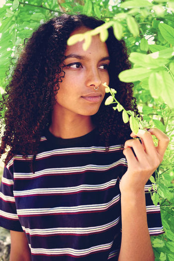 Thoughtful Young Woman Looking Away By Plants At Park