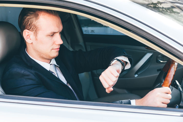 Businessman Checking Time While Driving Car