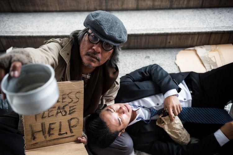 Portrait Of Beggar Asking For Help While Drunk Businessman Lying On Roadside