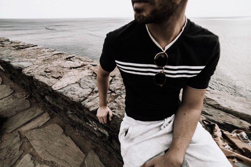 One Person Lifestyles Real People Leisure Activity Beach Land Midsection Front View Water Sitting Day Sea Nature Casual Clothing Young Adult Young Men Men Standing Outdoors #FREIHEITBERLIN