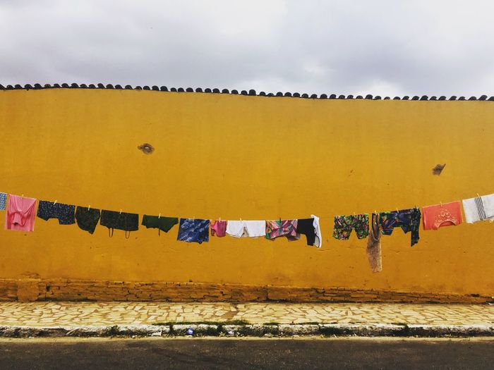Clothes drying outdoors against yellow wall
