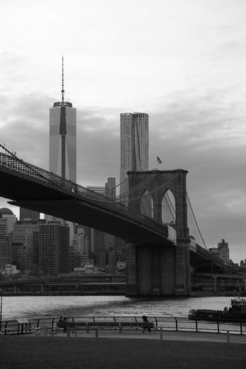 Brooklyn bridge over east river by one world trade center against sky