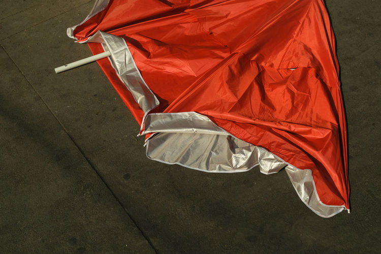 High angle view of red umbrella fallen on road