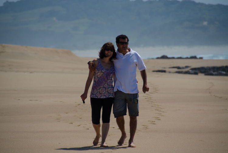 Smiling Mid Adult Couple Walking At Sandy Beach
