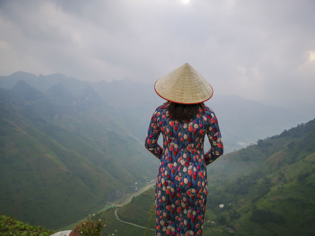 Young Vietnamese women facing and pose for camera with stunning view of the Nho Que river surrounded by mountains from the Ma Pi Leng pass in northern Vietnam Mountain Cloudy Green Color Meo Vac Vietnam Vietnamese Adult Ao Dai Beauty In Nature Day Hat Idyllic Landscape Leisure Activity Lifestyles Looking At View Mountain Mountain Range Nature Non-urban Scene One Person Outdoors People Pose Real People Rear View Scenics - Nature Standing Sunrise Three Quarter Length Traditional Dress Tranquil Scene Tranquility Valley Women