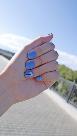 Close-Up Of Woman With Blue Nail Polish On Fingernails