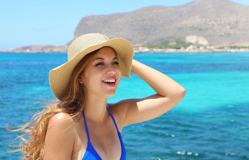 View of smiling young woman in hat against sea