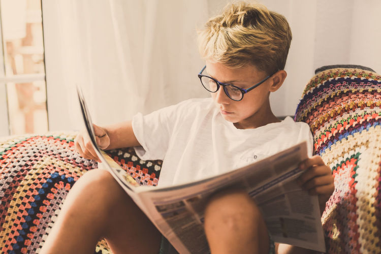 Boy reading newspaper while sitting at home