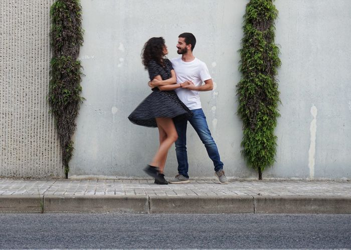 Full length portrait of young couple dancing against wall
