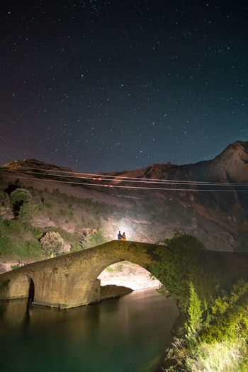 Couple standing on arch bridge over river at night