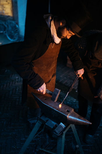 Blacksmith  Christmas Iron Workshop Adult Anvil Concentration Day Fire Hammer Holding Indoors  Manual Worker Men Metal Industry Occupation One Person People Real People Skill  Standing Working Workshop Business Stories