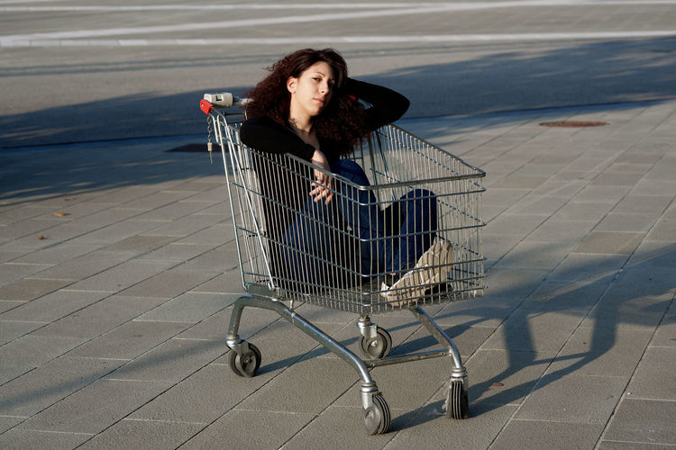 Portrait of woman sitting in shopping cart