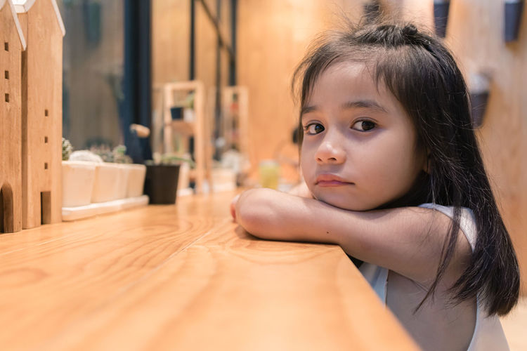 Portrait of cute girl looking away at table