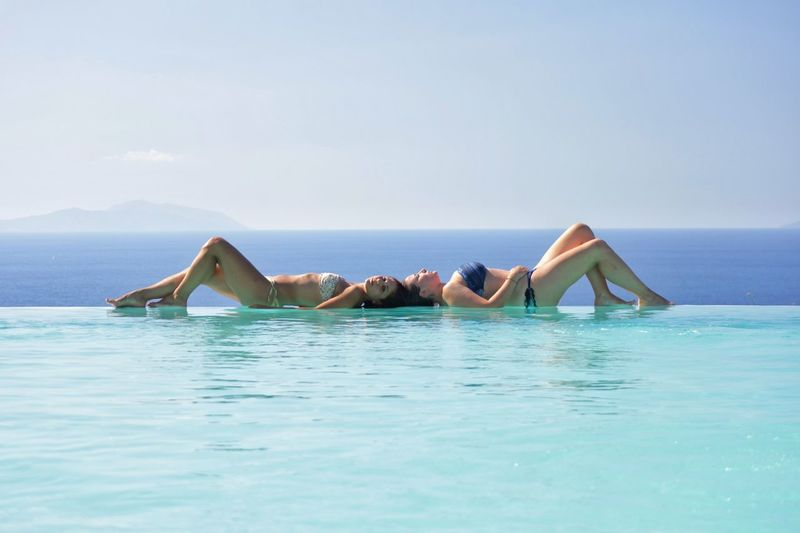 Side view of females lying on infinity poolside against sky