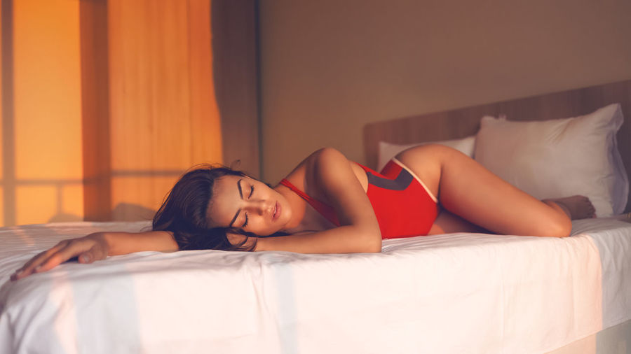 Tired beautiful young woman falling asleep in bed after relaxing day at pool