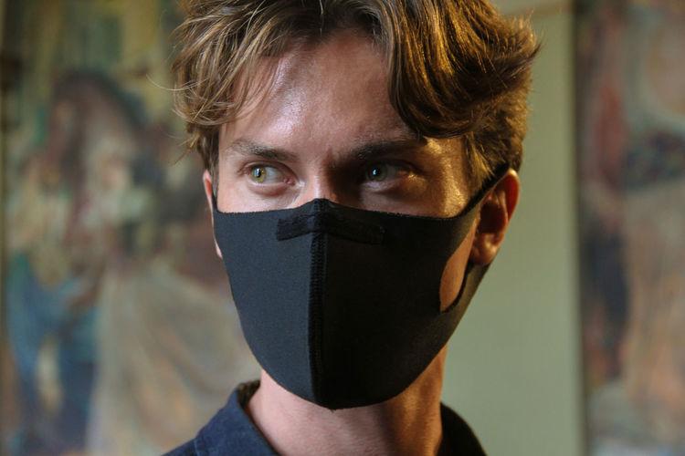 Close-up of man wearing mask looking away