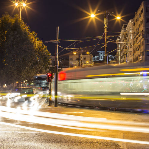 Blurred Motion Of Cable Car On Road In City At Night