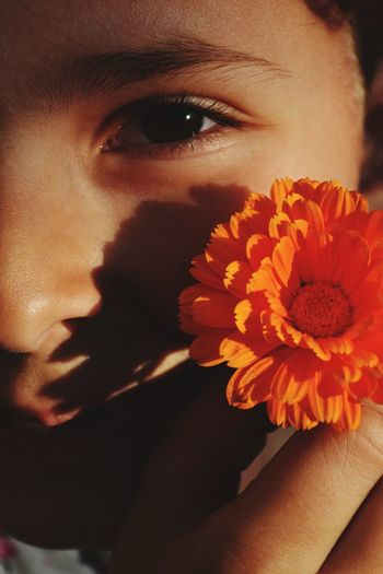 Close-up portrait of girl holding orange flower