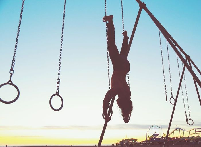 Man Hanging Upside Down On Outdoor Gymnastic Rings