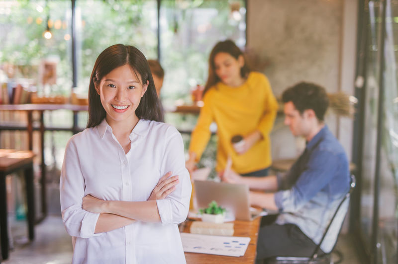 Portrait of businesswoman smiling while working with coworkers in cafe