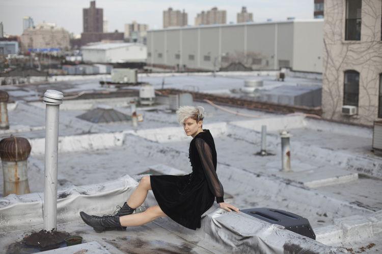 Woman sitting on floor in city