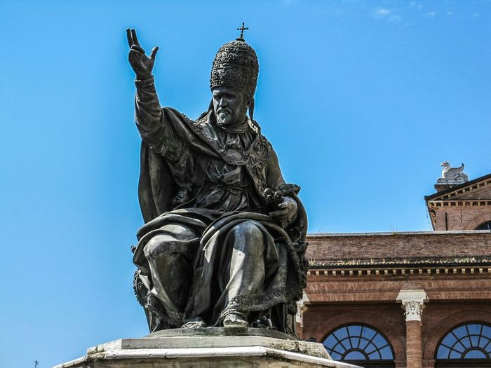 Low Angle View Of Old Statue By Church Against Sky
