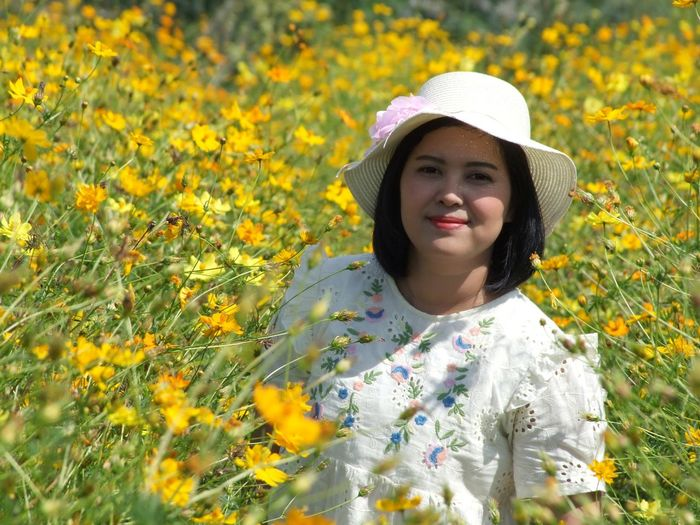 Portrait of beautiful young woman standing by yellow flowering plants