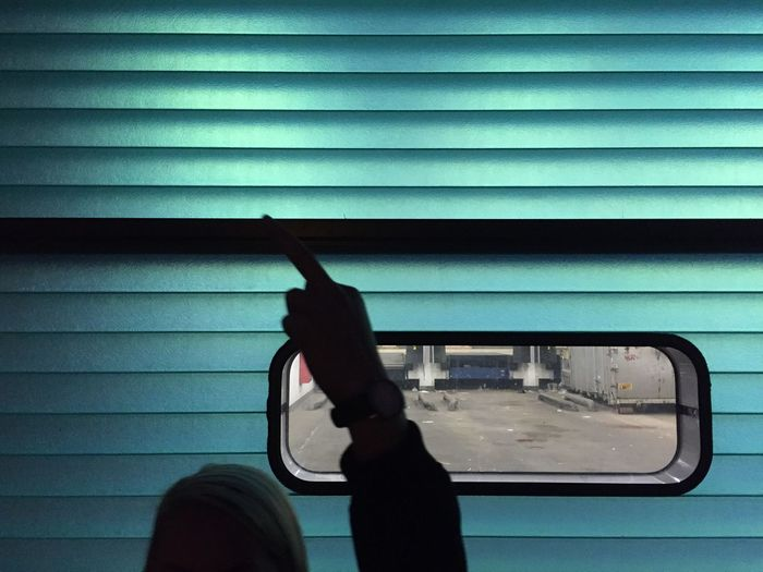 Silhouette man gesturing against window amidst turquoise wall