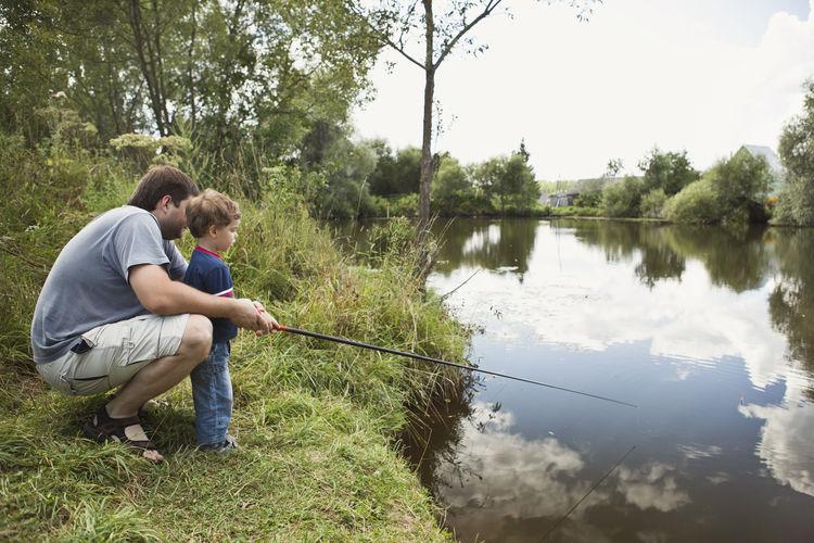 Man sitting on fishing rod by lake
