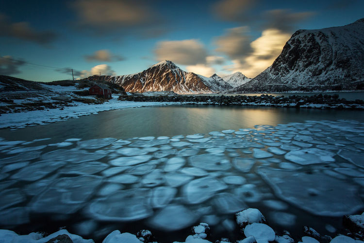 Scenic view of frozen lake by snowcapped mountains