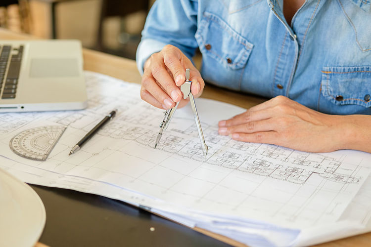 Midsection of architect making blueprint at desk