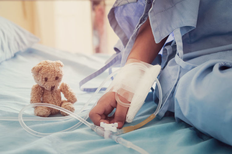 Midsection of patient sitting by teddy bear on hospital bed