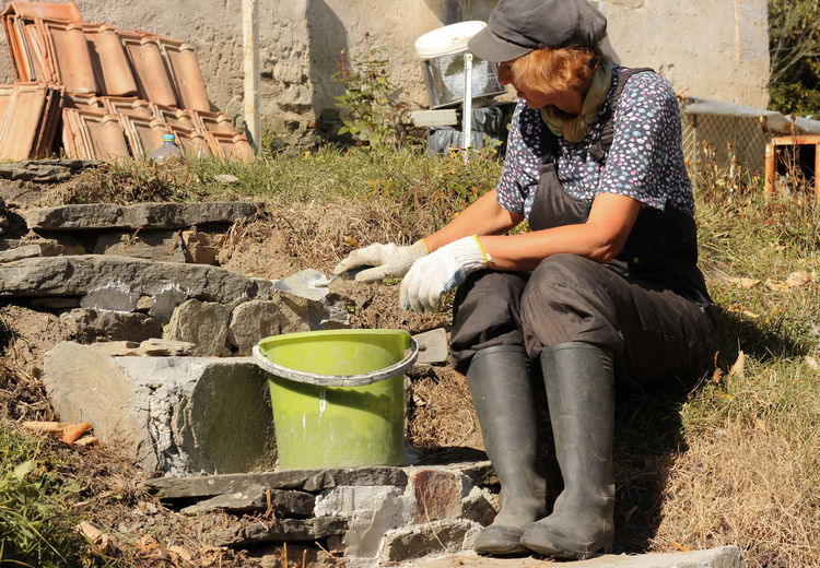 Senior woman working while sitting by cement bucket outdoors
