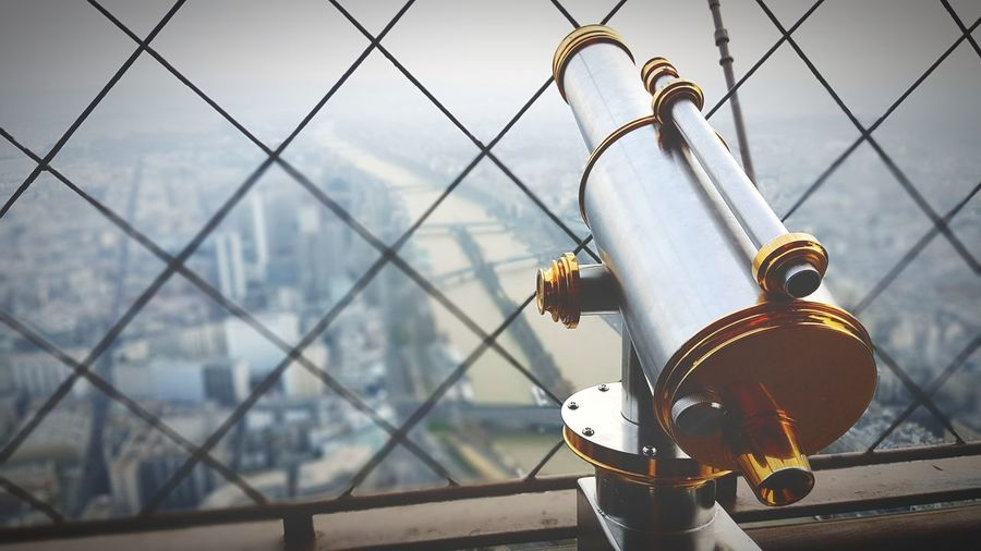 Coin-operated binoculars by chainlink fence in eiffel tower overlooking city