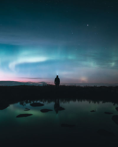 Man with flashlight standing under sky at night