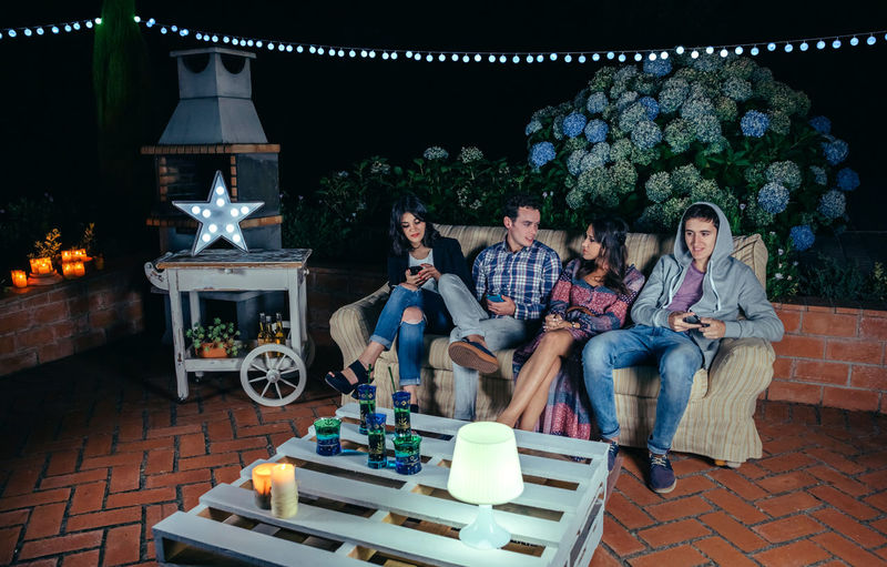 Happy young friends drinking and having fun in a outdoors party. Friendship and celebrations concept. Celebration Friends Fun Happiness Happy Horizontal Lights Millenials Sitting Terrace Young Alcohol Cheerful Drink Entertainment Four People Friendship Group Night Nightlife Outdoors Party People Sofa Star