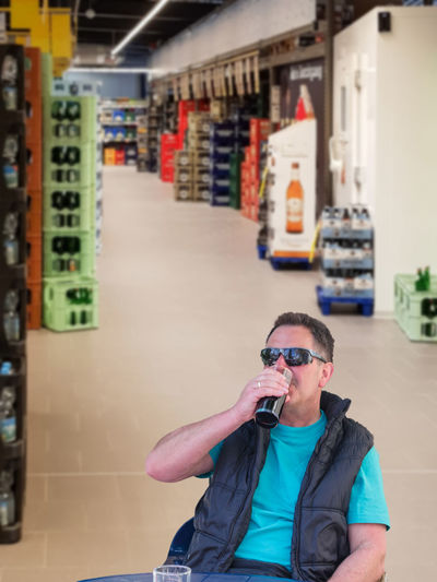 Portrait of a man in the drinks shop with glass in hand while tasting wine. Background intended blur. Architecture Built Structure Casual Clothing Fashion Front View Holding Indoors  Leisure Activity Lifestyles Males  Men One Person Photographing Photography Themes Portrait Real People Sunglasses Technology Young Adult