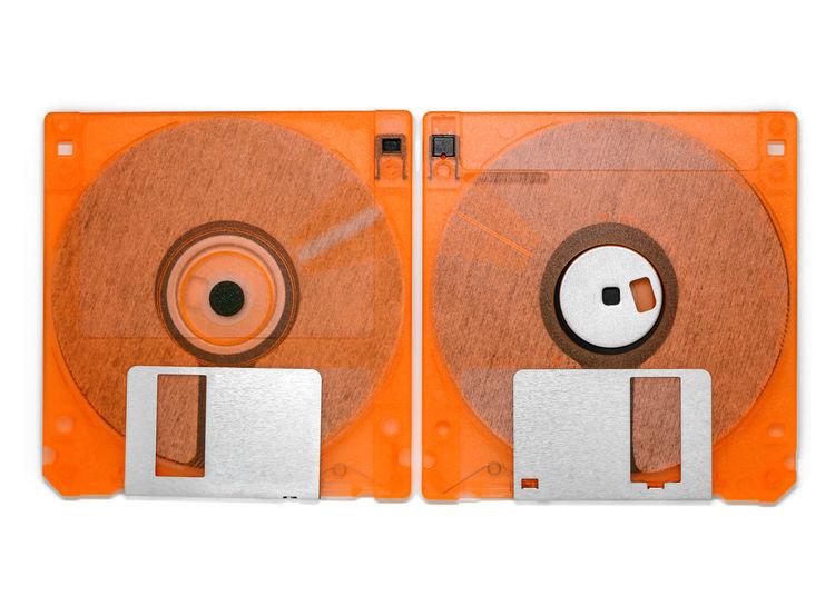 1980s 1990s 90s Backup File Floppy Obsolete Computer Data Device Disk Diskette Floppy Disk  Information Old Orange Color Storage Technology White Background