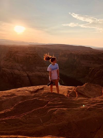Woman tossing hair while standing on rock formation against sky during sunset